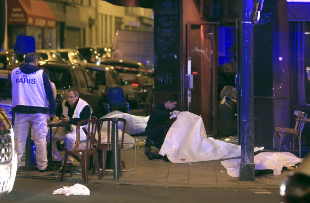 Victims lay on the pavement outside a Paris restaurant, Friday, Nov. 13, 2015.  Police officials in France on Friday report multiple terror incidents, leaving many dead.  It was unclear at this stage if the events are linked. (AP Photo/Thibault Camus)